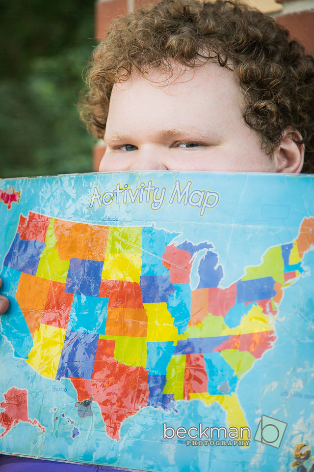 Nathan, who has autism, poses with one of his favorite maps for a senior picture.